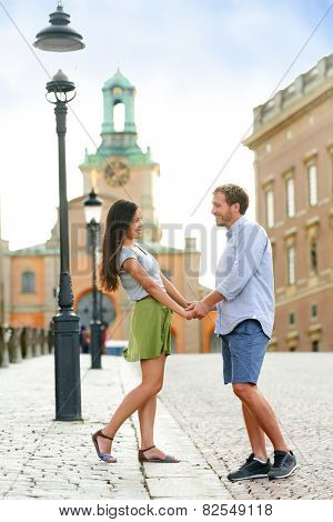 Couple in love holding hands in Stockholm city. Urban people lifestyle of two young adults dating and flirting in the street in front of The Royal Palace and the Cathedral in Gamla Stan, Sweden.