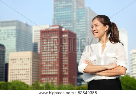 Asian businesswoman portrait in Tokyo. Happy confident young smart professional in casual business outfit in Japanese downtown Tokyo with skyline in the background.