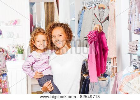 Smiling small girl with her mother shopping