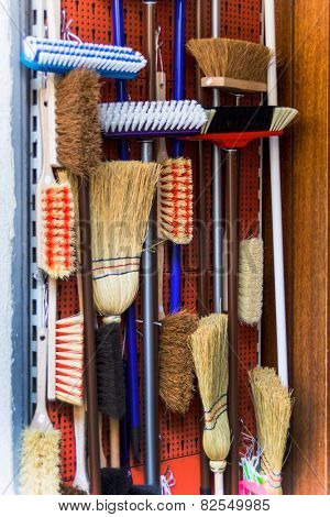 cabinet with different types of brooms