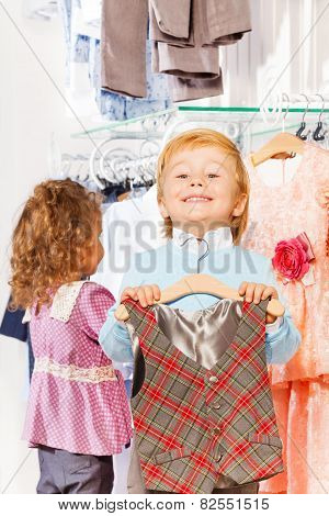 Close-up view of boy with hanger and girl behind