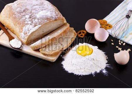 Still life of bread, eggs, flour and kitchen tools on a blackboard