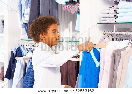 Small African boy in white shirts choosing clothes