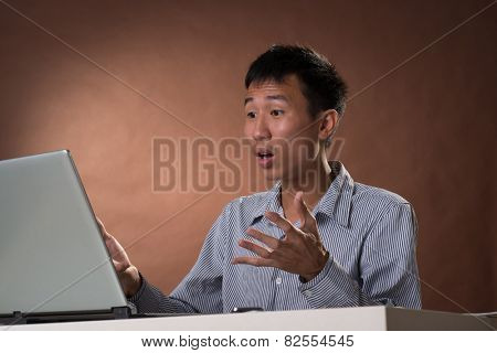 Surprised Chinese business man sitting on chair and looking at laptop in studio.