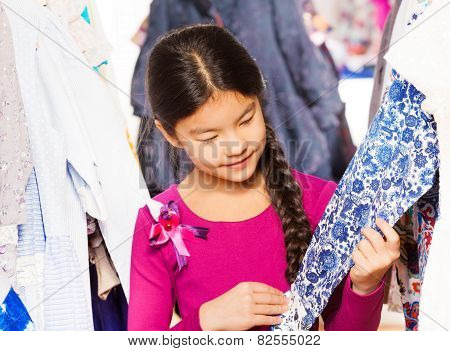 Asian girl with braid choosing and looking at item