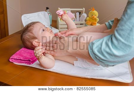 Mother massaging body of her baby lying