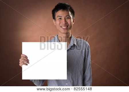 Young business guy of Chinese holding blank board in studio.
