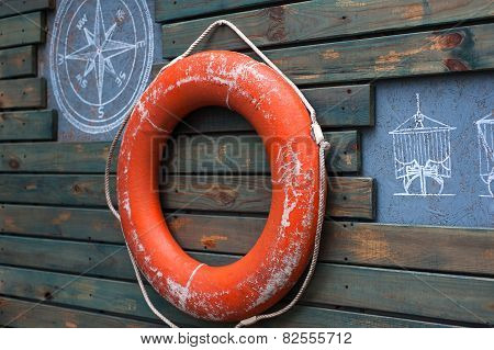 Red lifebuoy hanging on a wooden wall