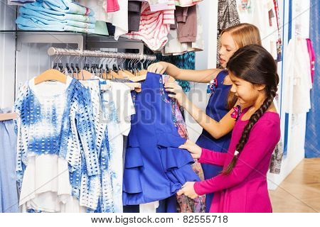 Two small girls shop together in the clothes store