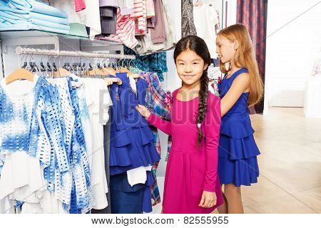 Two small girls shopping together and smiling
