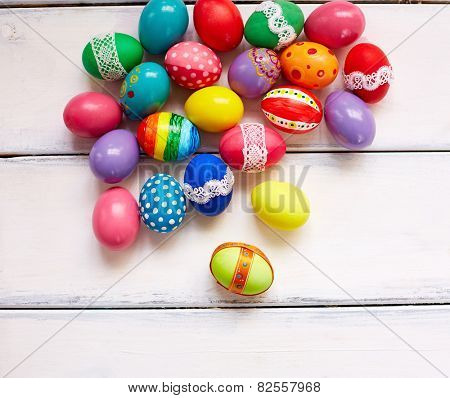 Creatively painted Easter eggs on white wooden background