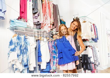 Girl with her mother shopping and hold chosen item