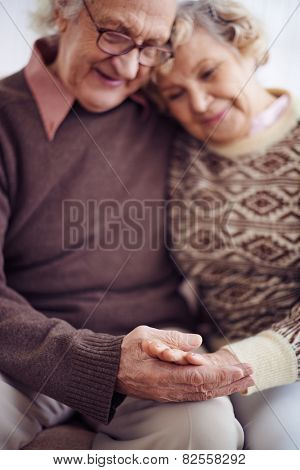Hands of devoted seniors in sweaters