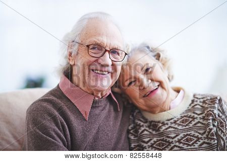 Two happy pensioners looking at camera with smiles