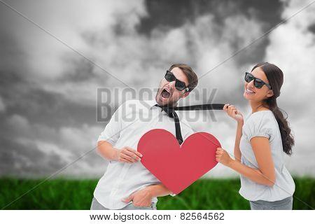 Brunette pulling her boyfriend by the tie holding heart against green grass under grey sky