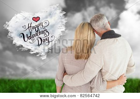 Happy couple standing with arms around against cloud heart