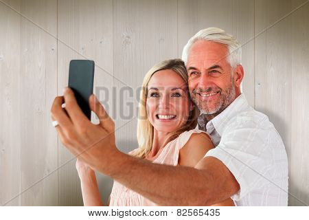 Happy couple posing for a selfie against wooden planks