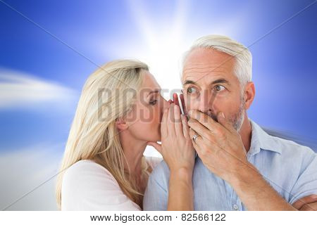Woman whispering a secret to husband against large rock overlooking bright sky