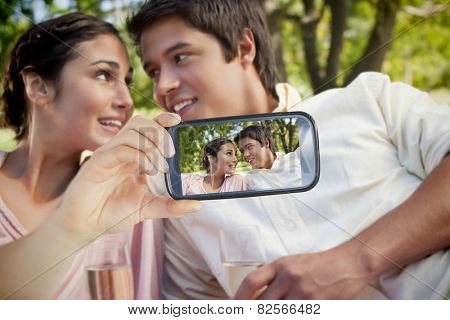 Composite of Couple taking selfie on smartphone