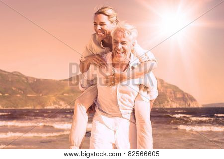 Man giving his laughing wife a piggy back at the beach on a sunny day