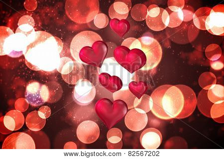 Floating love hearts against twinkling red and orange lights