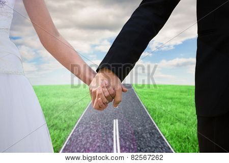 Mid section of newlywed couple holding hands in park against road on grass