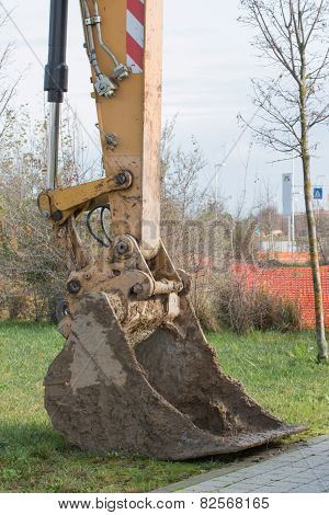 Closeup Of Muddy Excavator Shovel On Grass Near Construction Area