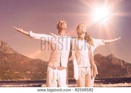 Happy couple standing with arms outstretched at the beach on a sunny day