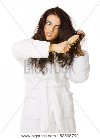 Young displeased girl with hairbrush isolated