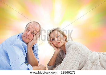 Mature couple lying and thinking against girly pink and yellow pattern