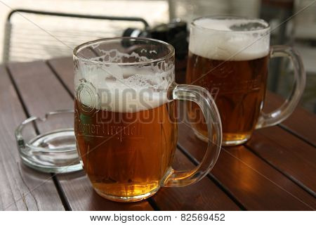 PRAGUE, CZECH REPUBLIC - MAY 13, 2014: Two mugs of traditional Czech beer Pilsner Urquell seen in a pub in Prague, Czech Republic.