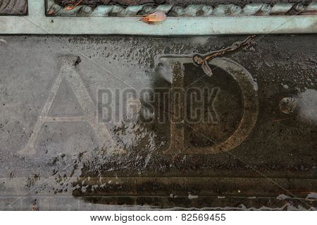 A.D. Anno Domini. Inscription on a bronze gravestone at an abandoned cemetery in Central Bohemia, Czech Republic.