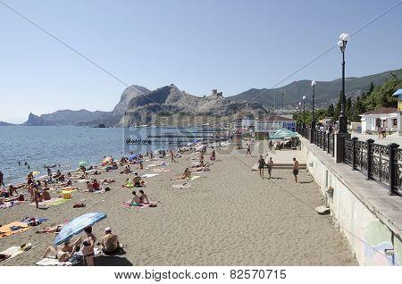 People Sunbathe And Swim On The Beach In Sudak In The Crimea