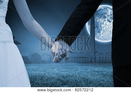Mid section of newlywed couple holding hands in park against bright moon over paris