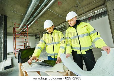 young male engeneers workers foreman at a indoors building site with blueprints