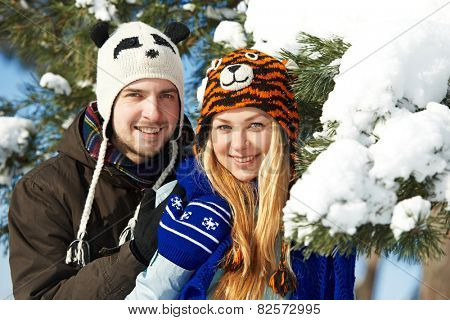 happy young smiling adult people in warm clothing at winter snow outdoors