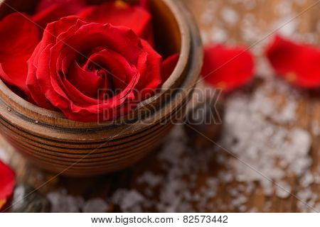 Roses in bowl with pile of salt ,stones on old wooden board