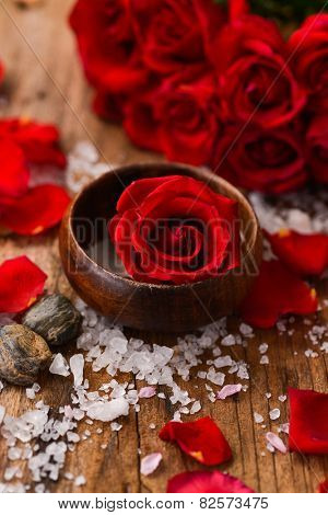 Lying down rose with roses in bowl with pile of salt ,stones on old wooden board
