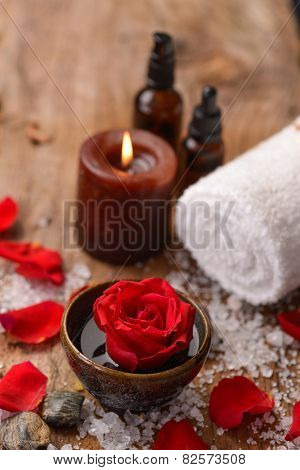 roses in bowl with pile of salt ,stones ,oil,towel,candle on old wooden board