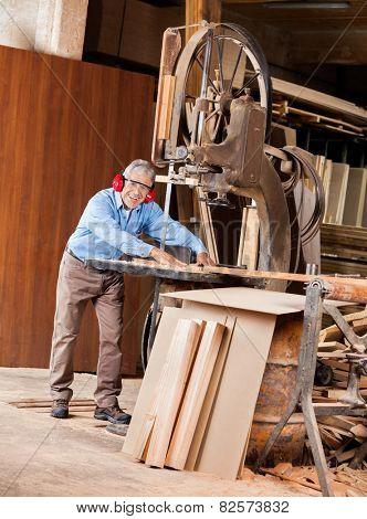 Full length portrait of happy senior male carpenter using bandsaw in workshop
