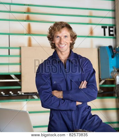 Portrait of confident carpenter in uniform standing arms crossed against vertical panel saw