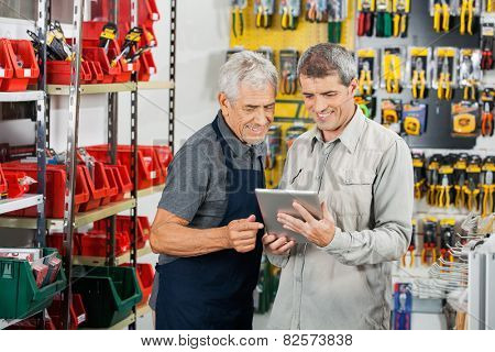 Salesperson and customer using tablet computer in hardware store