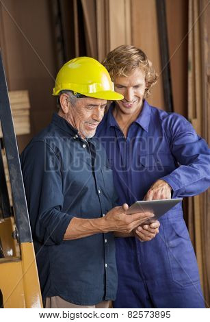 Male carpenters using tablet computer together in workshop