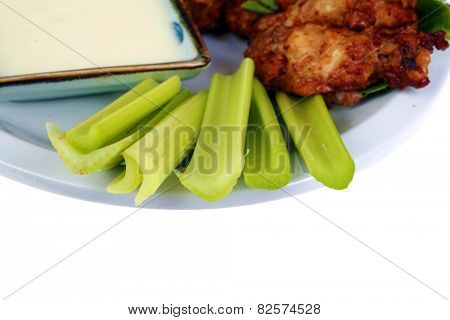 Buffalo Chicken Wings with Celery and Blue Cheese Dressing and Lettuce on a White Plate isolated on white with room for your text. Buffalo Wings are enjoyed by millions of people around the world.