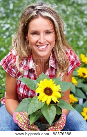 Gardening woman. Girl working in garden with flowers.