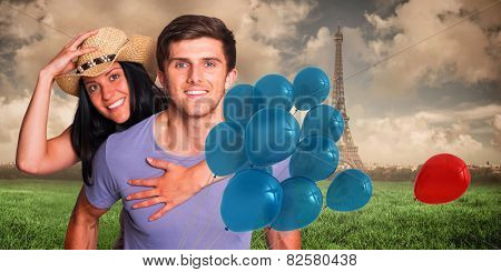 Man giving his pretty girlfriend a piggy back against paris under cloudy sky