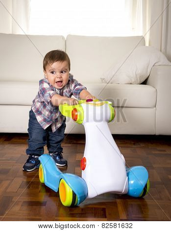 Sweet Little Boy Playing Alone With Baby Walker Taking His First Steps Excited And Playful