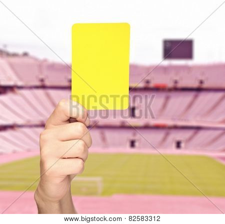 Hand showing a yellow card in front of an empty stadium shot with tilt and shift lens