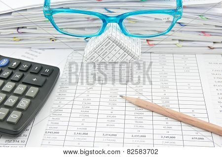 Brown Pencil And Blue Glasses On House With Finance Account