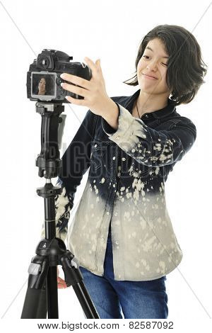 An attractive young teen critiquing adjustments on her pro camera, hoping to get a great selfie.  Her image is visible on the camera's viewing screen.  On a white background.